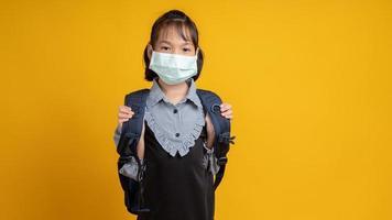 asiatisches Mädchen trägt Gesichtsmaske mit Rucksack, der Kamera mit gelbem Hintergrund betrachtet foto