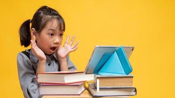 thailändisches Mädchen sieht überrascht aus, wenn es Tablette auf Stapel von Büchern mit gelbem Hintergrund betrachtet foto