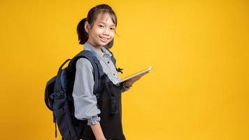 junges asiatisches Mädchen, das einen Rucksack trägt und Tablette hält, die Kamera mit gelbem Hintergrund betrachtet foto