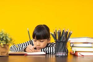 junges asiatisches Mädchen, das in einem Notizbuch neben Stapel Bücher, Tasse Bleistifte und Blumen mit gelbem Hintergrund schreibt foto