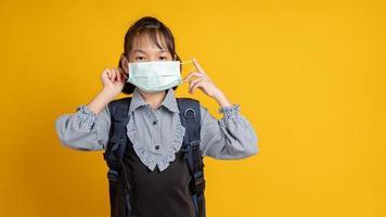 junges asiatisches Mädchen, das eine Gesichtsmaske und einen Rucksack trägt, die Kamera mit gelbem Hintergrund betrachten foto