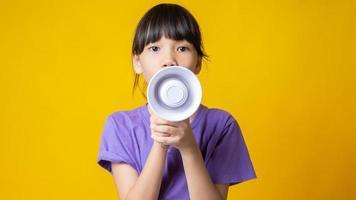 junges asiatisches Mädchen lächelnd im lila Hemd, das weißes Megaphon im Studio mit gelbem Hintergrund hält foto