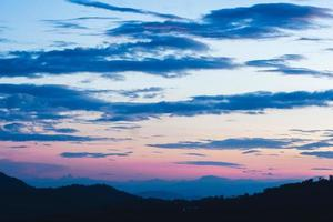 bunter bewölkter Sonnenuntergang über Bäumen und Bergen