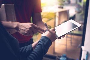 Mann zeigt auf Tablette, während Frau es unterschreibt foto