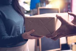 Nahaufnahme der Frau, die einfach verpackte Schachtel oder Paketpaket von den zwei Händen eines Mannes erhält foto