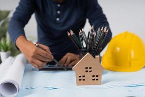 Architekt arbeitet an einer Blaupause neben Schutzhelm, Tasse Bleistift und Hausmodell foto