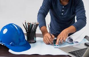 Architekt arbeitet an einer Blaupause neben Laptop, Schutzhelm, Tasse Bleistift und gerolltem Papier foto
