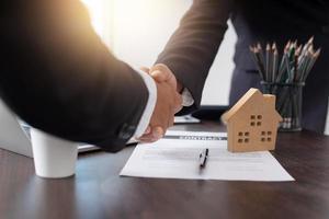 Nahaufnahme von Geschäftsleuten, die Hände über Schreibtisch mit Vertrag und Hausmodell schütteln