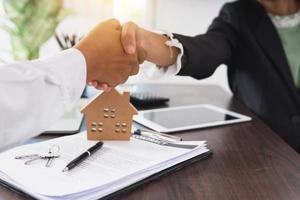 Nahaufnahme von Geschäftsfrau und Mann, die Hände über Schreibtisch mit Vertrag und Hausmodell schütteln