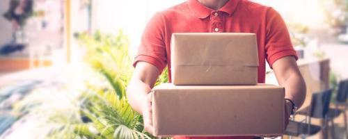Lieferbote hält zwei Kisten oder Pakete mit unscharfem Außenterrassenhintergrund foto