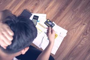 Schließen Sie die Hand des Mannes, der eine Kreditkarte mit Papieren und einem Taschenrechner an einem Schreibtisch hält foto