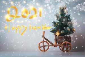 Weihnachtsbaum auf einem Holzauto mit einem glücklichen neuen Jahr 2021 Text foto