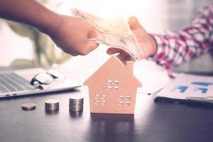 Zwei Hände tauschen Geld neben dem Hausmodell, dem Laptop und den Münzstapeln aus foto