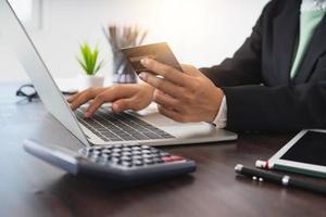 Geschäftsfrau, die Kreditkarte hält und auf einem Laptop neben Taschenrechner an einem braunen hölzernen Schreibtisch tippt