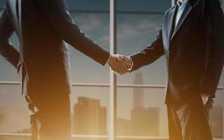 Nahaufnahme von Geschäftsleuten, die Hände mit unscharfer Stadtskyline im Hintergrund schütteln foto