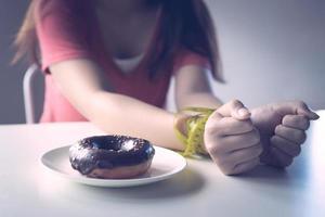 Frau mit Händen gebunden mit einem Maßband neben einem Donut auf einem weißen Teller foto