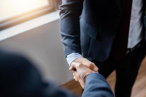 Nahaufnahme von Geschäftsleuten, die Hände mit unscharfem Hintergrund schütteln foto