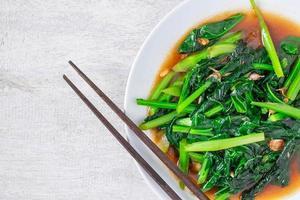 gebratener chinesischer Grünkohl mit Austernsauce mit Stäbchen auf einem weißen Teller auf Holztisch foto