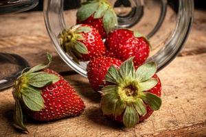 Erdbeeren in einem Glas auf einem Holztisch foto