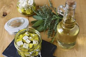 marinierter Feta in einem Glas, Gewürzen und Olivenöl auf einem hölzernen Hintergrund foto