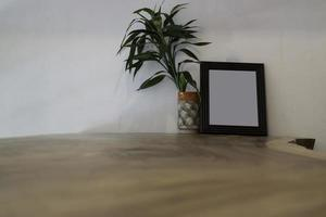leerer Rahmen verspotten mit Pflanze auf Tisch foto