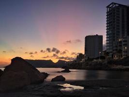 Wohnungsturm an einem ruhigen Strand bei Sonnenuntergang foto