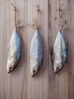 Fisch hängt zum Trocknen auf Holz foto