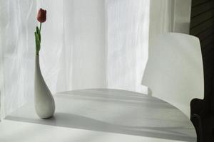 Blumenvase mit hellem Licht aus dem Fenster foto