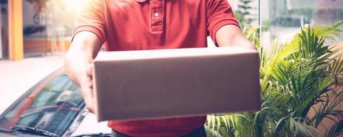 Lieferbote hält eine verpackte Schachtel oder ein Paket foto