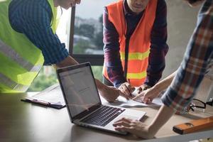 Drei Ingenieure zeigen auf eine Blaupause neben einem Laptop foto
