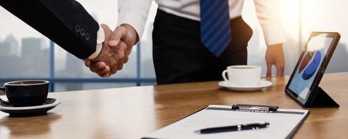 Geschäftsleute, die Hände neben Schreibtisch mit Kaffeetassen und Tablette Händeschütteln foto