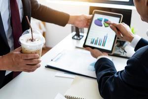 Geschäftsleute, die Diagramme und Grafiken auf einem Tablett betrachten foto