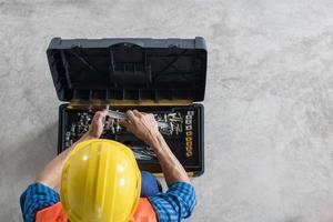 Bauarbeiter, der Werkzeuge über einen Werkzeugkasten handhabt foto