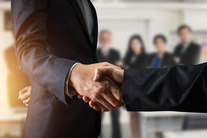 zwei Geschäftsleute, die Händeschütteln mit unscharfen Leuten im Hintergrund schütteln foto