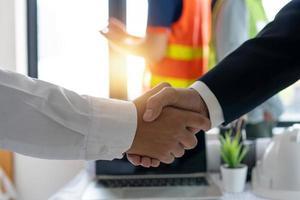 zwei Leute, die Händeschütteln mit unscharfem Bauarbeiter im Hintergrund schütteln
