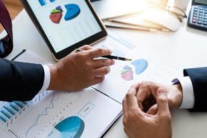 Nahaufnahme von zwei Geschäftsmannhänden neben Diagrammen und Grafiken auf Papier und Tablette