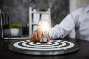 Geschäftsmann, der beleuchtete Glühbirne auf einer Dartscheibe auf einem schwarzen Schreibtisch hält