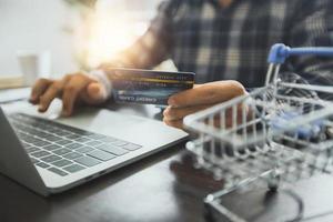 Mann hält Kreditkarte und arbeitet an einem Laptop neben Miniatur-Einkaufswagen