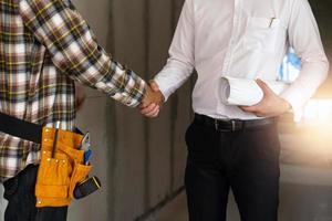 Bauarbeiter Händeschütteln mit Geschäftsmann hält aufgerollte Papiere foto