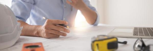 Geschäftsmann arbeitet an Blaupause neben Laptop-Maßband, Schutzhelm und Fenster