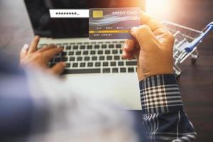 Nahaufnahmehand des Mannes, der Kreditkarte hält und am Laptop neben Miniatur-Einkaufswagen arbeitet