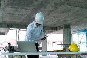 Mann im Schutzhelm, der an einem Laptop und einem Tablett an einem Schreibtisch an einem Bauanblick arbeitet foto