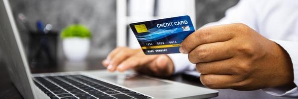 Nahaufnahmehand des Mannes, der Kreditkarte hält und am Laptop arbeitet