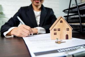 Person, die den Vertrag neben dem Musterhaus und den Schlüsseln unterzeichnet foto