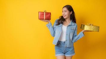 asiatische Frau, die rote und goldene Geschenkboxen auf gelbem Hintergrund hält foto