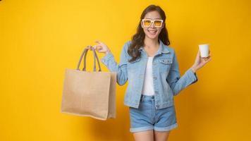 asiatische Frau, die Papiereinkaufstasche und weiße Pappbecher auf gelbem Hintergrund hält
