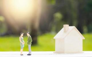 Miniaturfiguren des Mannes und der Frau neben Modellhaus mit unscharfem Naturhintergrund
