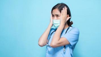 asiatische Frau in der blauen medizinischen Uniform, die eine Gesichtsmaske und ein Stethoskop trägt, das mit Händen gegen Seite ihres Kopfes gegen blauen Hintergrund gestikuliert foto