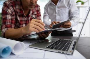 Geschäftsleute arbeiten neben Blaupausen an Tablets und Laptops