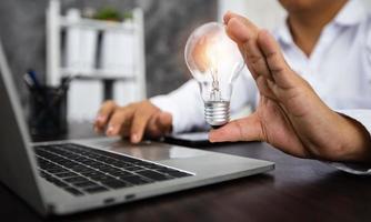 Mann, der am Laptop arbeitet und beleuchtete Glühbirne hält foto